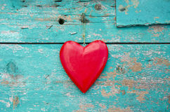 Häng det röda trähjärtasymbolet på den gamla grungeväggen Fotografering för Bildbyråer