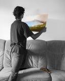 Hänga en färgrik målning på den tomma vita väggen Arkivfoto