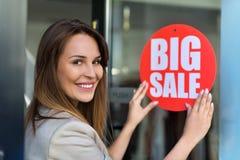Hängande försäljningstecken för kvinna på dörr Royaltyfri Bild