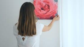 Hängande målning för ung kvinna på väggen stock video