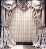 hänger upp gardiner det lyxiga fönstret Arkivbild