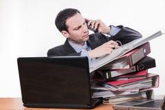 Hängiven anställd som kontrollerar mappen på telefonen Royaltyfria Bilder