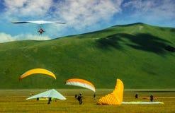 Hängningglidflygplan och paragliders i Castelluccio Royaltyfri Fotografi