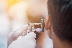 HNOarzt, der patient& x27 überprüft; s-Ohr unter Verwendung des Otoscope mit einem inst stockbild