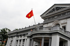 Ho Chi Minh City Museum. Exterior of the Ho Chi Minh City Museum - travel and tourism. Tourist standing next to the national flag Royalty Free Stock Photography