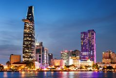 Ho Chi Minh City and the Saigon River at night. Ho Chi Minh City skyline and the Saigon River. Colorful night view of skyscraper and other modern buildings at stock photo