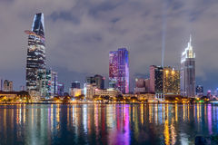 HO CHI MINH CITY SAIGON/VIETNAM - CIRCA AUGUSTI 2015: Ljus av Saigon i stadens centrum horisont reflekteras i floden Arkivfoton