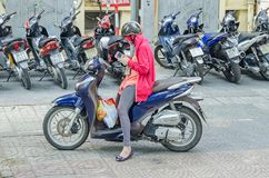 Young woman on her moped with helmet, face mask, gloves, and sm Stock Image