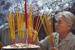 Woman with lit incense sticks. HO CHI MINH CITY, VIETNAM - February, 6 : A senior woman places smoking incense sticks into an urn within the Thien Hau Temple in Stock Images