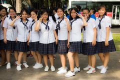 Ho Chi Minh city, Vietnam, 21.03.2018 - Nine young vietnamese girls satying in line in school uniform on street royalty free stock photography