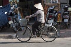 HO CHI MINH CITY VIETNAM-NOV 3RD: En kvinna cyklar ner en gata Arkivbild