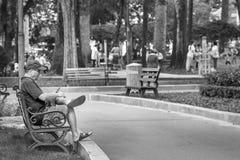 Ho Chi Minh City, Vietnam - September 1, 2018: een niet gedefiniëerde oude mens rust en luistert aan muziek in het park in de och stock fotografie