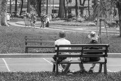 Ho Chi Minh City, Vietnam - September 1, 2018: twee niet gedefiniëerde oude mensen rusten en spreken in het park in de ochtend stock afbeelding