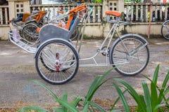 Ho Chi Minh City, Vietnam - September 1, 2018: Vietnamese cyclos en de vorm van een niet gedefiniëerde mens in de rug die een ond stock afbeelding