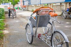 Ho Chi Minh City, Vietnam - September 1, 2018: Vietnamese cyclos en de vorm van een niet gedefiniëerde mens in de rug die een ond stock foto's