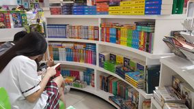 Ho Chi Minh city, Vietnam: Two pupils are reading books in the bookstore. Chi minh city vietnam two pupils reading books bookstore active activity paper table royalty free stock image