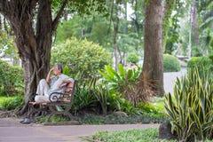Ho Chi Minh City, Vietname - 1º de setembro de 2018: um homem indeterminado que senta-se em um canto do parque que pensa sobre al foto de stock royalty free