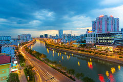 Ho Chi Minh Riverside cityscape night view with Ben Nghe or Tau Hu canal and calmet Bridge Stock Photo