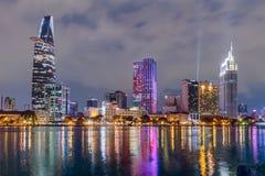 HO CHI MINH, SAIGON/VIETNAM - CIRCA AGOSTO 2015: Le luci dell'orizzonte del centro di Saigon sono riflesse nel fiume Fotografie Stock
