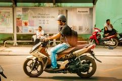 Ho Chi Minh stad, VIETNAM - MARS 29, 2017: män som kör en sparkcykel som är utomhus- i den Ho Chi Minh staden, Vietnam, retro fil Royaltyfri Foto