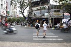HO CHI MINH STADT, VIETNAM - 24. Februar 2017: Leute kreuzen die Straße herein Stockfotografie