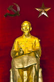 Ho Chi Minh statue in red background with Hammer and sickle. Royalty Free Stock Images