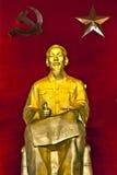 Den Ho Chi Minh statyn i röd bakgrund med bultar och skäran. Royaltyfria Bilder