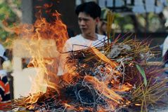 Plenty of incense sticks burn during religious ceremony with a man at the background in Ho Chi Minh, Vietnam. Royalty Free Stock Photography