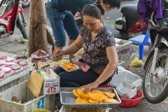 HO CHI MINH, VIETNAM - 17 GIUGNO 2015: Una donna non identificata sbuccia e vende la frutta del durian fotografie stock