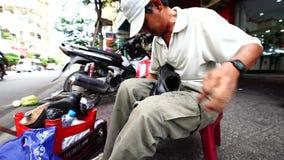 HO CHI MINH VIETNAM November 08, den vuxna mannen som arbetar på en gata nära den ben thanhmarknaden, att sy, sular av skorna man lager videofilmer