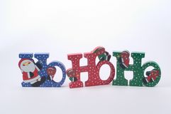 Ho Ho Ho. Christmas decoration of the whimsical fashion,  tree pieces spelling Ho Ho Ho with christmas figure adorning the letters.  Wooden bookshelf decoration Stock Images
