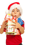 Ho!Ho!Ho!. Little kid boy with santa hat holding many Christmas gifts in his arms isolated on white background Royalty Free Stock Photos