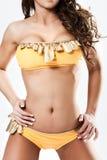 Hoad babe i gult bikiniföljeanseende Royaltyfria Bilder