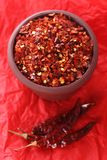 Hoade röda krossade chilichilir pepprar på rött fotografering för bildbyråer
