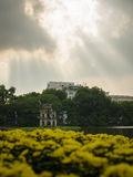 Hoan Kiem Lake with blur flower foreground and sunlight Stock Image