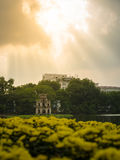 Hoan Kiem Lake with blur flower foreground and warmlight Stock Photography
