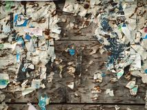 Hoarding. A collage of poster scraps and nails at old wooden wall Royalty Free Stock Photo