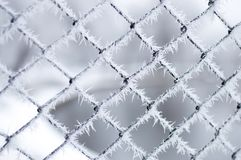 Hoarfrost on metal fence mesh. Hoarfrost on metal fence mesh with bokeh background Stock Photo