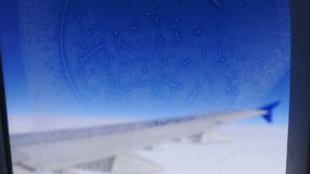 Hoarfrost Window Airplane Wing Travel 4k. Travel concept: hoarfrost on the aircraft window on the background of blue sky stock video