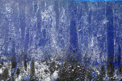 Hoarse, scratched, peeled surface with blue, white and black pai Stock Image