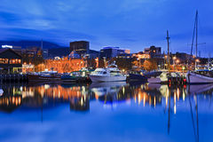 Hobart Harbour Yacht Gallery. Australia Tasmania Hobart sullivan's cove at sunset illuminated buildings gallery and docked yachts with lights Stock Photos