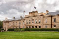 Hobart, Tasmania, Australia - December 13, 2009: Brown-stone Parliament house downtown under heavy cloudscape and green lawn up. Front. Flag and yellow flowers stock photos