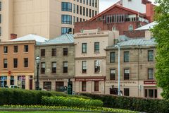 Hobart, Tasmania, Australia - December 13, 2009: Customs House hotel behind historic facades as part of hotel. Green park up front. Street scene stock photo