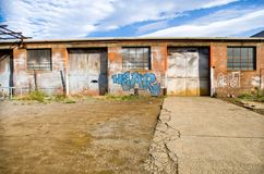 Abandoned car repair workshop. Hobart, Tasmania, February 6, 2016: Exterior view of an abandoned Car repair workshop, with grafitti on walls, Hobart, Tasmania Royalty Free Stock Image