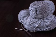 Hobbies and creative activities concept - three skeins of gray yarn with metal circular knitting needles on a wooden surface, royalty free stock images