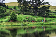 Hobbiton movie set. Hobbit holes in hobbiton movie set reflecting in a small lake. Taken in New Zealand Royalty Free Stock Image