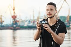 When hobby becomes beloved work. Portrait of dreamy creative young guy with beard holding camera and looking aside with royalty free stock photos