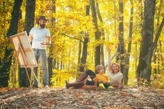 Hobby concept. Painter artist with family relaxing in forest. Painting in nature. Start new picture. Beauty of nature. Bearded men women and cute son relaxing stock image