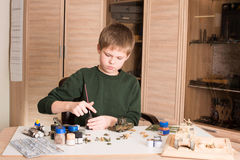 Hobby concept. Teen boy assembling and painting plastic model ta Stock Photo