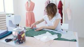 Hobby e piccola impresa Giovane sarto femminile che lavora con il tessuto del panno in officina video d archivio